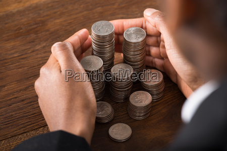 businessperson hand protecting pile of coins