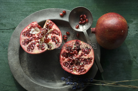 two halves of pomegranate on tin