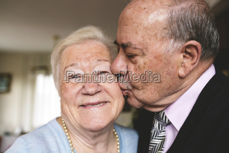senior man kissing his happy wife