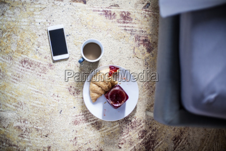 smartphone cup of coffee and croissant