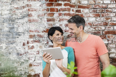 smiling couple sharing digital tablet