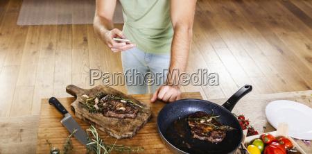 man with prepared steaks in kitchen