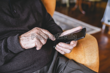 hands of senior man using smartphone
