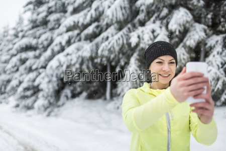 woman on snowy road taking picture