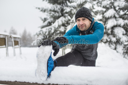runner stretching leg on snow covered
