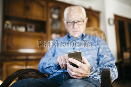 senior man using smartphone at home