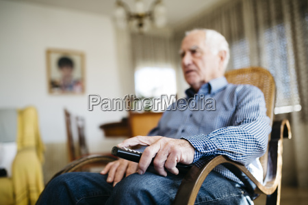 hand of senior man holding remote