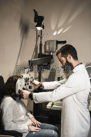 optometrist examining woman with a phoropter