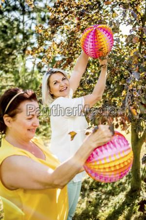 two mature women hanging up lampions