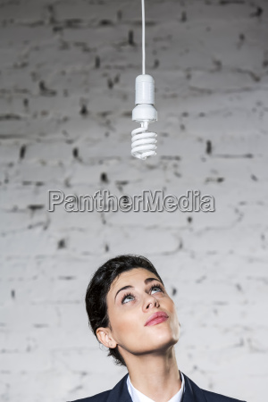 businesswoman looking up at energy saving