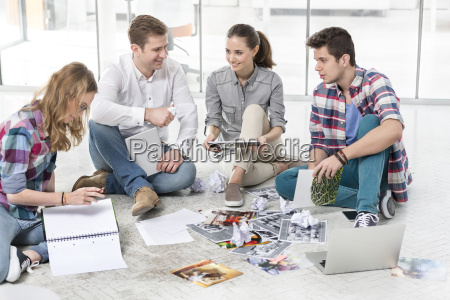 colleagues in office sitting on floor