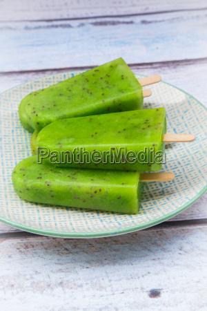 plate of homemade kiwi ice lollies