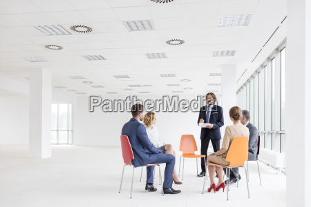 businessman talking to colleagues sitting in