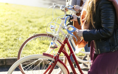 two young women strolling with bicycles