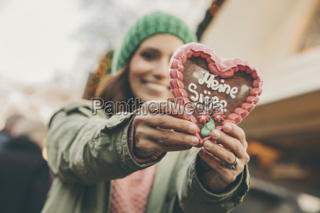 woman holding up a gingerbread heart