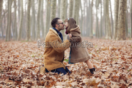 father kissing his daughter in park