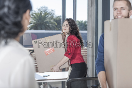 people in office with moving boxes