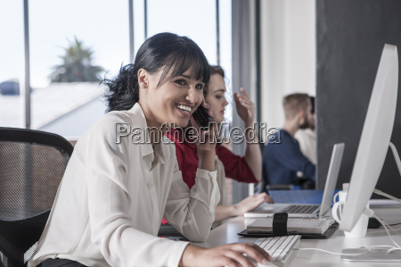 woman in office talking on the