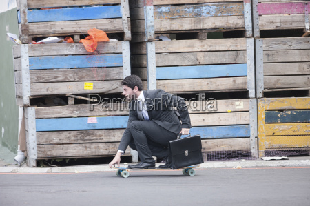 businessman riding on skateboard