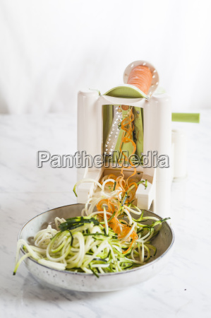 spiral vegetable slicer cutting zucchini and