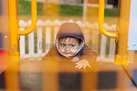 portrait of little boy climbing on