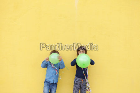 two little boys with green balloons
