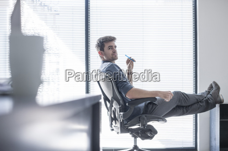 businessman in office with feet up