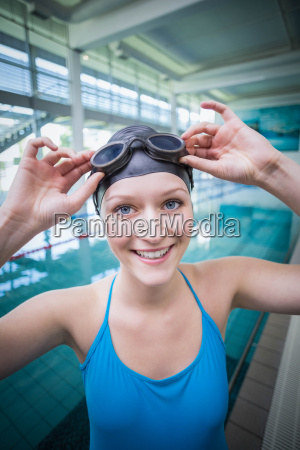 pretty woman putting on swimming goggles