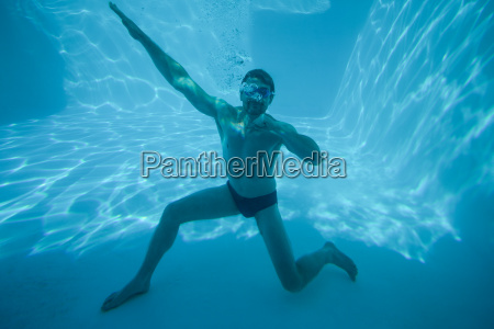 man posing underwater in swimming pool