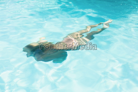 beautiful woman swimming in swimming pool