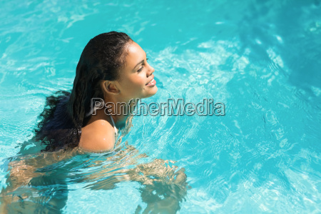 beautiful woman in white bikini swimming