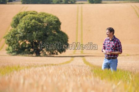 farmer standing in sunny rural barley