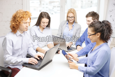 smiling team with laptop and table