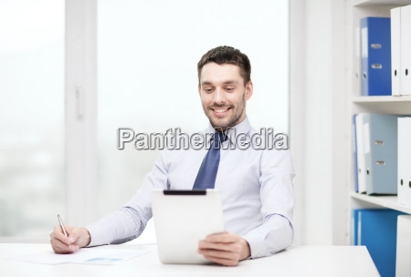 smiling businessman with tablet pc and