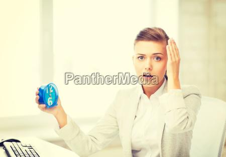 stressed businesswoman holding clock