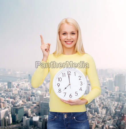 student with wall clock and finger