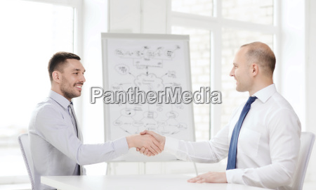 two smiling businessmen shaking hands in