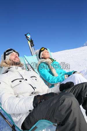couple of skiers sunbathing at top
