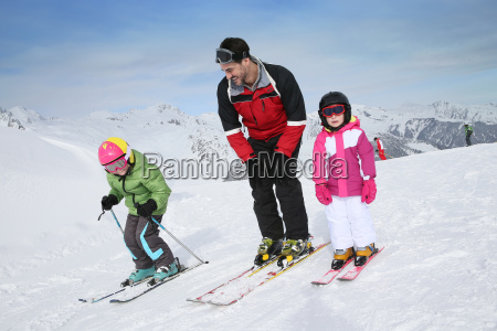 ski teacher helping young kids to