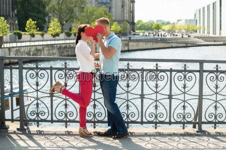 couple kissing behind heart shape