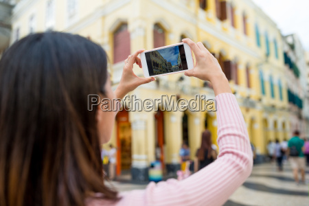 woman taking photo by cellphone in