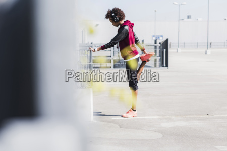 young woman stretching on parking lot