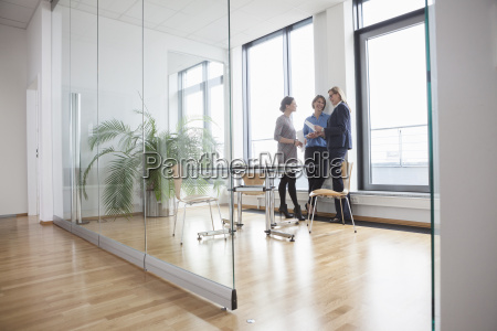 three businesswomen discussing at the window