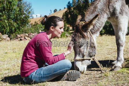 peru amantani island woman stroking donkey