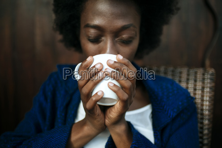 womans hands holding cup of coffee