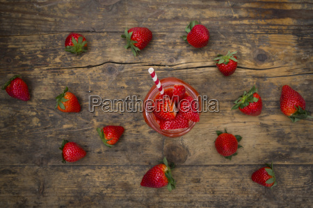 glass of strawberry smoothie and strawberries