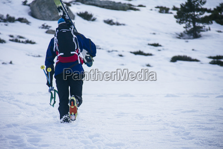 man with skis and backpack walking