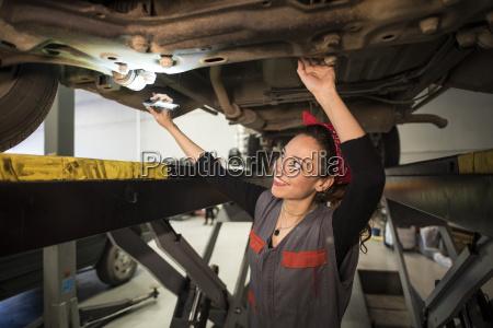 mechanic woman working under a car