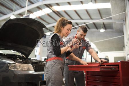 mechanics working in workshop reparing car
