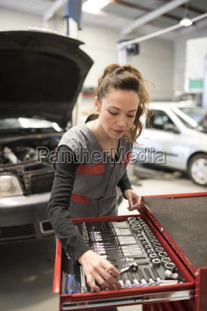 woman working in workshop taking tool